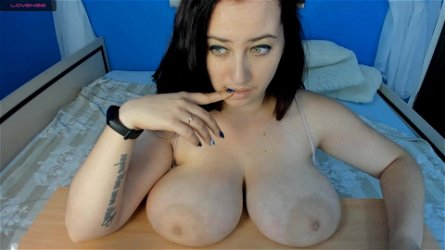Green eyed brunette puts big boobs and areolas on the table